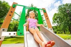 Charming girl on playground chute ready to slide Stock Image