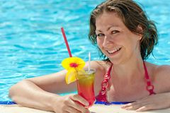 Charming girl in the pool and a glass of alcoholic cocktail Stock Photo