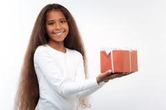 Charming girl posing on white background with gift box. Happy birthday. Beautiful pre-teen girl with a swarthy complexion and long auburn hair posing on a white Stock Image