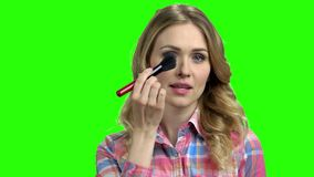 Charming girl puts on makeup on the green screen. Beautiful woman preens before a date. Chroma Key background stock footage