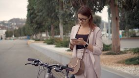 Charming girl is reading and sending messages, standing outdoors in city. Young woman is using smartphone in city street. She is parked her bike and standing stock footage