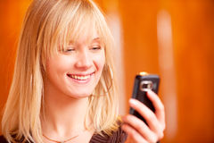 Charming girl reads sms. On mobile phone and smiles Royalty Free Stock Photography