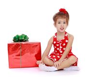 Charming girl in a red dress. Sitting on the floor in white socks near beautifully gift Packed- isolated on white background Royalty Free Stock Images