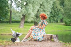 Charming girl with red hair in retro style posing in a vintage dress stock image
