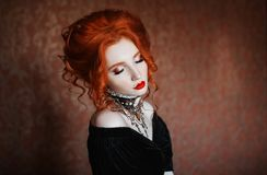 Charming girl with red hair. A woman is a vampire with pale skin and red hair in a black dress and a necklace on her neck. Girl witch with vampire claws and red royalty free stock images