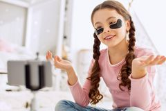 Charming girl reviewing under-eye patches in vlog. Informative vlog. Sweet pre-teen girl sitting cross-legged on the floor and reviewing under-eye patches in her Stock Image