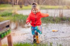 Charming girl running in big puddle Royalty Free Stock Images