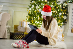 Charming girl in Santa`s cap sits nearby a Christmas tree with the laptop. Stock Photo