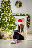 Charming girl in Santa`s cap sits nearby a Christmas tree with the laptop. Stock Photography
