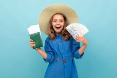 Charming Girl Shows A Passport With Tickets, Money And Rejoices Royalty Free Stock Photography