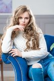 Charming girl sitting in living room on blue couch Stock Images