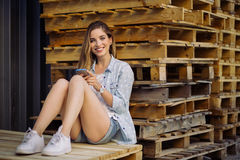Charming girl sitting on a pallet using smart phone Stock Images