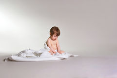 Charming girl sitting on white blanket, space for text royalty free stock photos