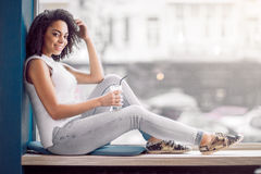 Charming girl sitting on the window sill Royalty Free Stock Photo