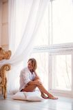 Charming girl  sitting on windowsill Royalty Free Stock Photo