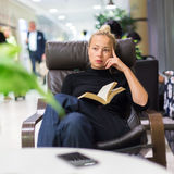 Charming girl sitting by wooden table and reading book. Thougtful woman sitting by wooden table and reading book in public library Stock Images