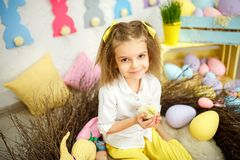 Charming little girl with small ducklings. Charming girl sitting with yellow soft chiken in hands looking at camera and smiling in Easter decoration Stock Photos