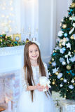 Charming girl smiling and posing at camera, holding candle on ba Royalty Free Stock Photos
