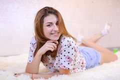 Charming girl smiling and posing, lying on carpet on floor in b stock images