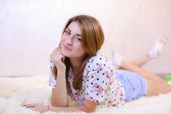 Charming girl smiling and posing, lying on carpet on floor in b stock photos