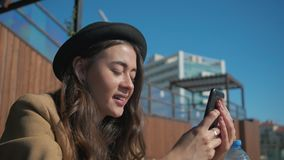 Charming girl on social media via smartphone outdoor. stock footage