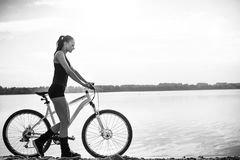 Charming girl in sportswear with a bicycle near the water Stock Photography