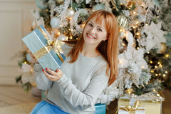Charming girl with straight hair smiling and holding a gift on a royalty free stock images