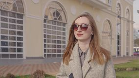 Pretty young woman is enjoying by walk in sunny spring day in city. Charming girl is strolling in small garden in spring day. She is wrapping into coat, turning stock footage