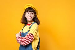Charming girl teenager in french beret, denim sundress holding hands folded, looking aside isolated on yellow wall. Background in studio. People sincere stock photography
