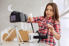Charming girl telling how to wear VR headset in vlog. Crucial advice. Beautiful joyful pre-teen girl telling her viewers how to wear a VR headset while recording Royalty Free Stock Images
