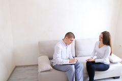 Young woman came to see doctor guy who listens and writes. Guy a Royalty Free Stock Photo