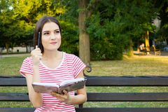 Charming girl thinking something while reading a book in the green park.  Stock Photo
