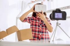 Charming girl trying out VR headset while filming vlog. Contemporary vlogger. Cute pre-teen girl trying out a VR headset and telling how to wear it while filming Stock Photos