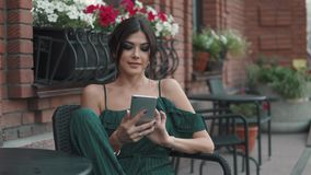 Charming girl uses a mobile phone sitting in a cafe outdoors in old town. young woman sends a message from smartphone. Portrait of young beautiful girl at sunset stock video footage