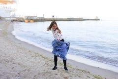 Charming Girl Walks Along Coast And Merrily Fools Around On Sand Stock Image