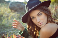 Charming girl wearing black hat with naked. Portrait of charming girl in black hat and green sweater. Young woman with naked shoulder looking at camera on fall Royalty Free Stock Photo
