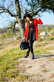 Charming girl wearing red coat with black handbag Stock Photo