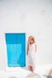 Charming girl in white dress outdoors in old streets an Mykonos. Kid at street of typical greek traditional village with Royalty Free Stock Photography