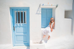 Charming girl in white dress outdoors in old streets an Mykonos. Kid at street of typical greek traditional village with Royalty Free Stock Photos