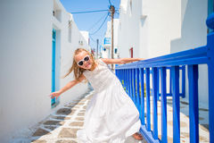 Charming girl in white dress outdoors in old streets an Mykonos. Kid at street of typical greek traditional village with Stock Image