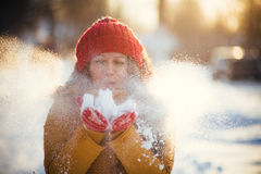 Charming girl in a yellow jacket and red cap throws snow in the air royalty free stock photography