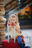 Charming girlie 7-8 years sits beside their luggage at the station. Girl pondered or tired. She sits, leaning on the handle of a suitcase. Tall stack of old stock photos