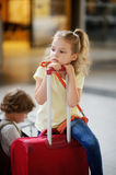 Charming girlie 7-8 years sits beside their luggage at the station. Girl pondered or tired. She sits, leaning on the handle of a suitcase. Behind her stock photos