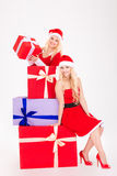 Charming girls in dresses of santa claus with colorful gifts Royalty Free Stock Image