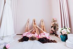 Charming girls lying upstairs with arms raised crossed legs, celebration of a birthday holiday event. stock photography