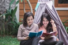 Bestfriend daily activity. Charming girls reading a book near a tent Royalty Free Stock Photo