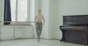 Graceful ballet dancer performing allegro exercise. Charming graceful ballerina rehearsing in ballet studio, performing allegro jump exersice. Elegant classic stock video footage