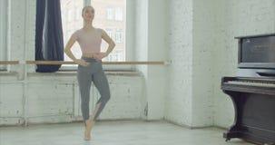 Ballet dancer performing temps lie exercise. Charming graceful ballerina rehearsing in ballet studio, performing temps lie exersice. Elegant classic ballet stock video footage