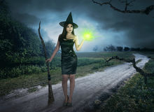 Charming halloween asian witch with magic light holding broom Stock Image
