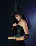 Charming halloween witch. With magic wand and book over black and blue background Royalty Free Stock Photography